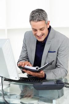 Улыбающийся бизнесмен, консультирующий свою программу
