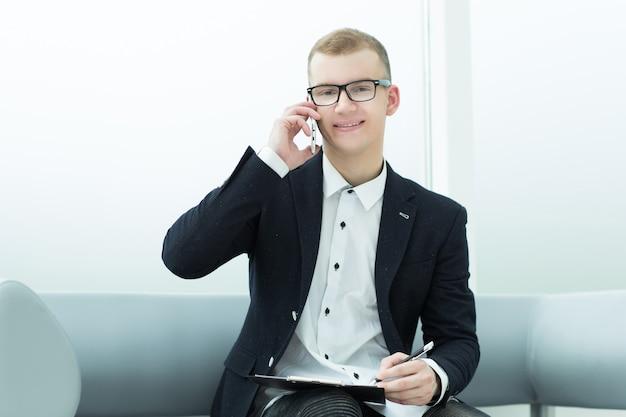 Улыбающийся бизнесмен что-то обсуждает по мобильному телефону