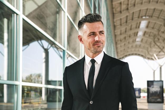 空港の外を歩くスーツを着たビジネスマンを笑顔