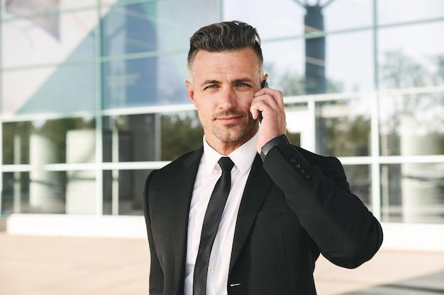 外を歩くスーツを着たビジネスマンを笑顔