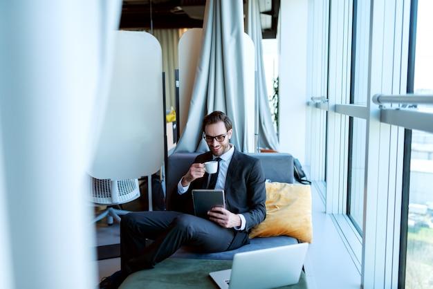 仕事でタブレットを使用してエレガントな服を着て、彼のオフィスのソファーに座っている間コーヒーを飲むビジネスマンの笑みを浮かべてください。