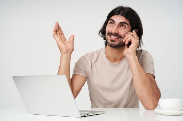 Uomo d'affari sorridente, uomo dall'aspetto felice con barba e capelli neri. concetto di ufficio. alza il palmo e parla al telefono. momenti di lavoro. seduto sul posto di lavoro, isolato vicino sopra il muro bianco