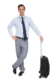 Smiling businessman next to his suitcase