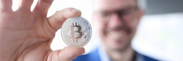 Smiling businessman holding bitcoin making money on bitcoins without investments concept
