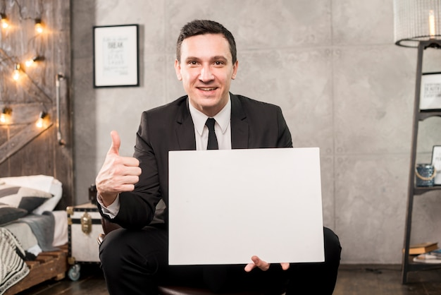 Smiling businessman holding blank paper and gesturing thumb up