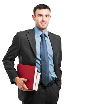 Smiling businessman holding books on white background