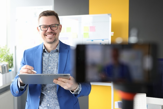 Smiling businessman holding clipboard and conducting online business