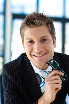 Smiling businessman holding glasses