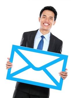 Smiling businessman holding sign of envelope