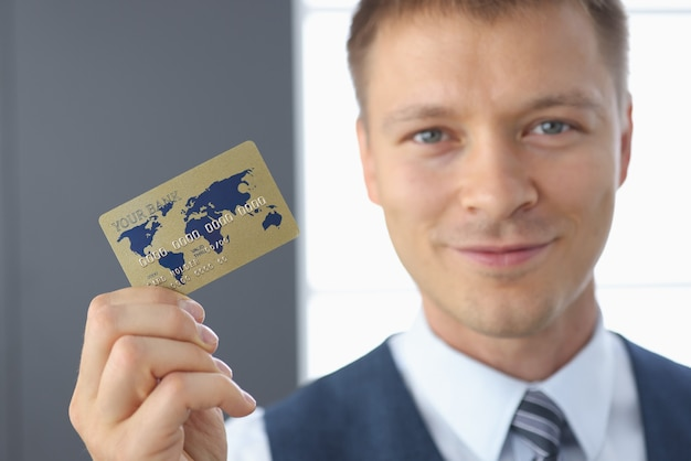 Smiling businessman holds plastic bank card in his hand