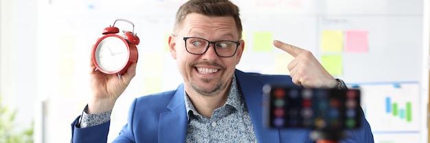 웃고 있는 사업가는 빨간색 알람 시계를 들고 온라인 시간 관리 과정 시간을 실시합니다