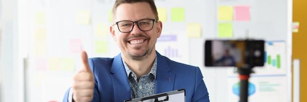 웃고 있는 사업가는 엄지손가락을 들고 비디오 개발에 대한 비즈니스 교육을 기록합니다.