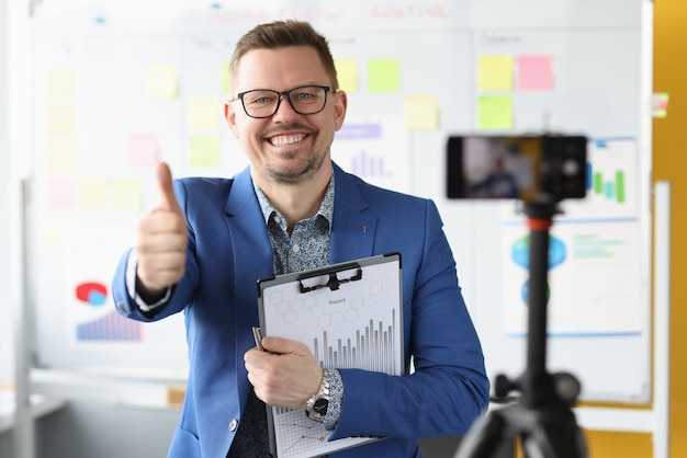 Smiling businessman holds thumbs up and records business training on video