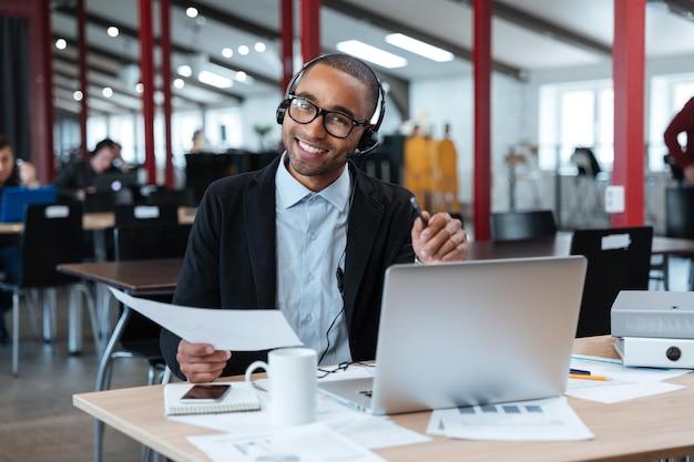 Улыбающийся бизнесмен в наушниках держит документы и указывая на вас в офисе
