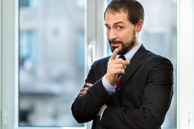 彼の指をあなたに向けて彼のオフィスで笑顔のビジネスマン