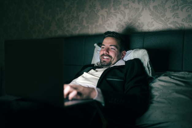 夜にホテルの部屋のベッドに横になっていると仕事にラップトップを使用してスーツのビジネスマンを笑っています。過労の概念。