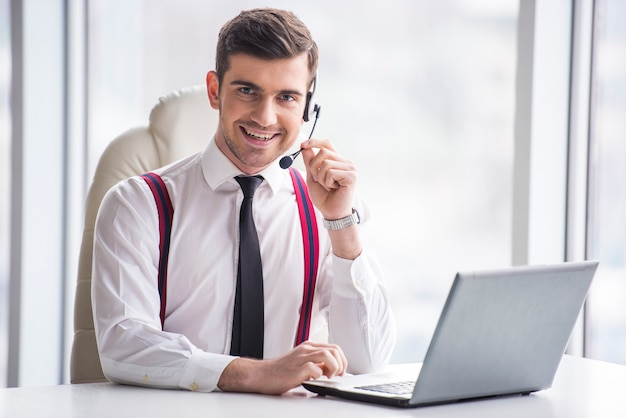 Smiling businessman is taking a call on a headset.