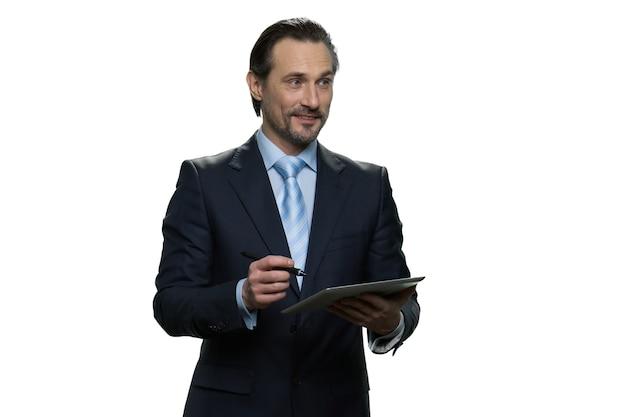 Улыбающийся бизнесмен пишет на планшете. успешный хорошо одетый человек с ручкой, изолированной на белой стене.