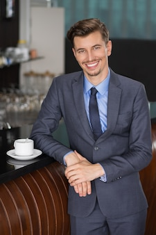 Smiling businessman leaning on cafe counter