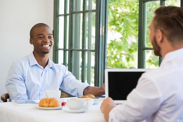 レストランで同僚を見ている笑顔のビジネスマン