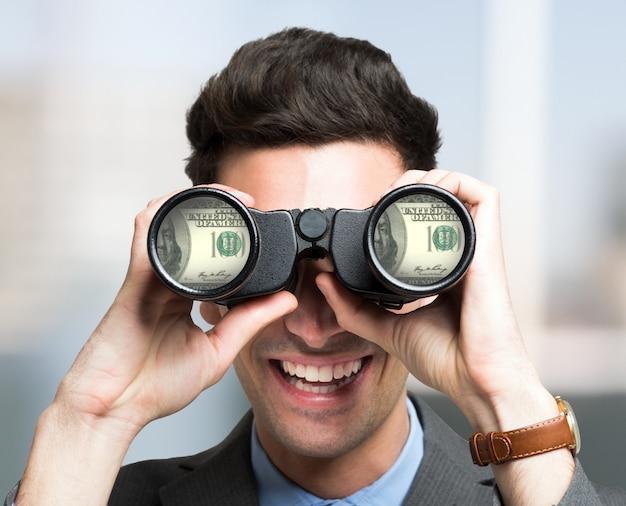 Улыбающийся бизнесмен, глядя на долларовые банкноты через бинокль