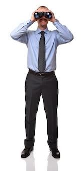Улыбающийся бизнесмен, глядя в классический бинокль на белом