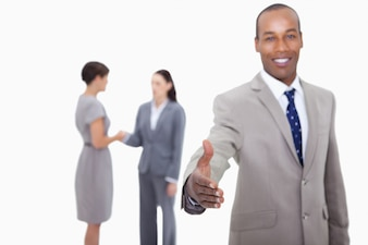 Smiling businessman offering his hand with hand shaking colleagues behind him against a white backgr
