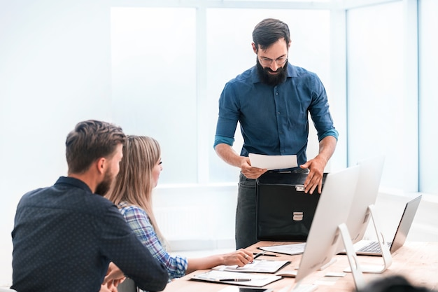 Улыбающийся бизнесмен передает документы рабочей группе. фото с местом для текста