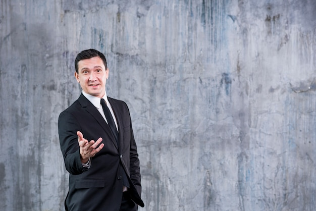 Smiling businessman pointing at camera while standing against grey wall