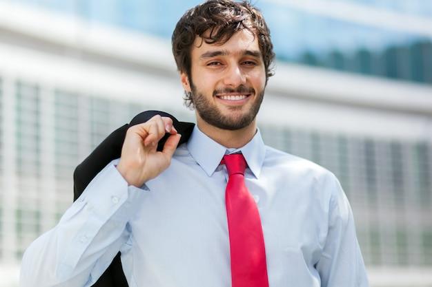 Smiling businessman portrait holding his jacket