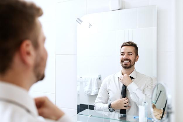 鏡で見ているとバスルームに立っている間ネクタイを履いて笑顔の実業家。