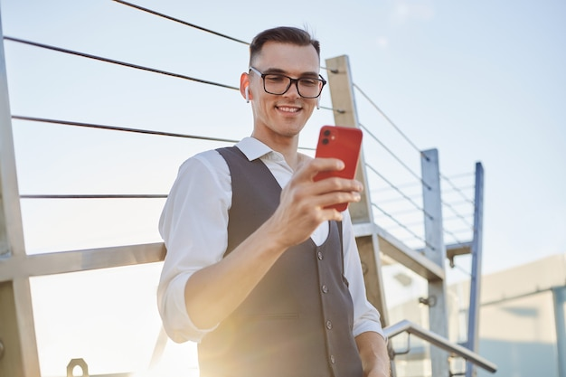 Smiling businessman reading a message on his smartphone.