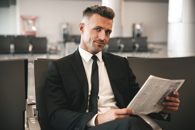 Smiling businessman reading newspaper