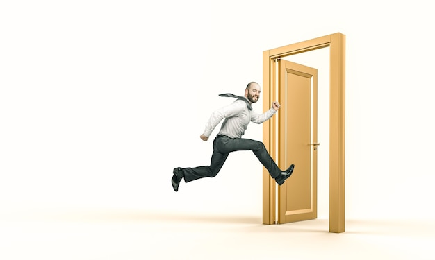 Smiling businessman runs and enters a gold door.
