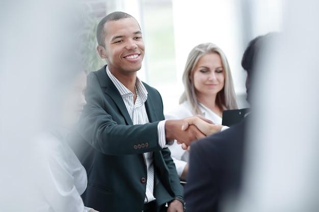 Улыбающийся бизнесмен, пожимая руку деловому партнеру. фотография с копией пространства