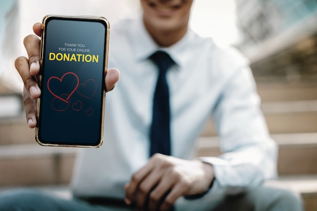 Smiling businessman showing a donate message