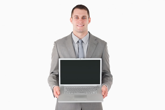 Smiling businessman showing a laptop