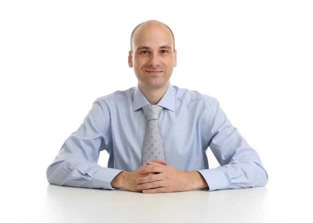 分離された白で分離された彼の机に座って笑顔の実業家