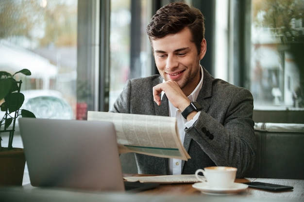Smiling businessman sitting by the table in cafe with laptop computer while reading newspaper