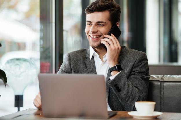 Smiling businessman sitting by the table in cafe with laptop computer while talking by smartphone
