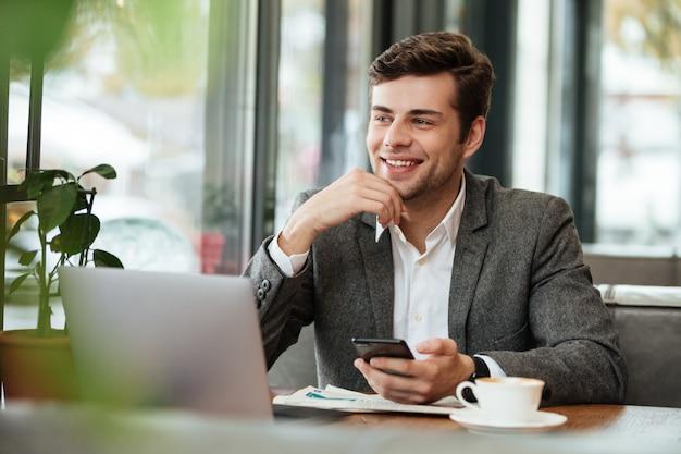 Улыбающийся бизнесмен, сидя за столом в кафе с ноутбуком и смартфоном, глядя в сторону
