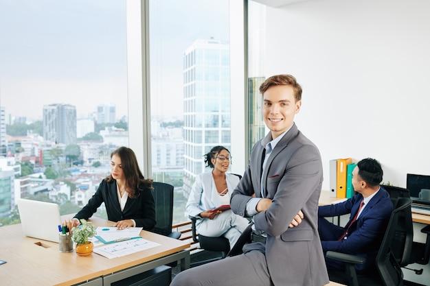 机の上に座っている笑顔の実業家
