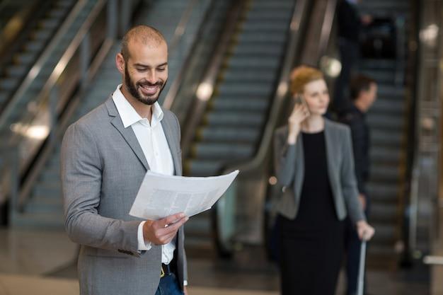 Улыбающийся бизнесмен, стоя в зоне ожидания, читая газету