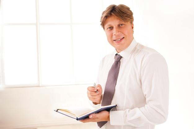 화이트에 일기를 들고 사무실에 서 있는 웃는 사업가