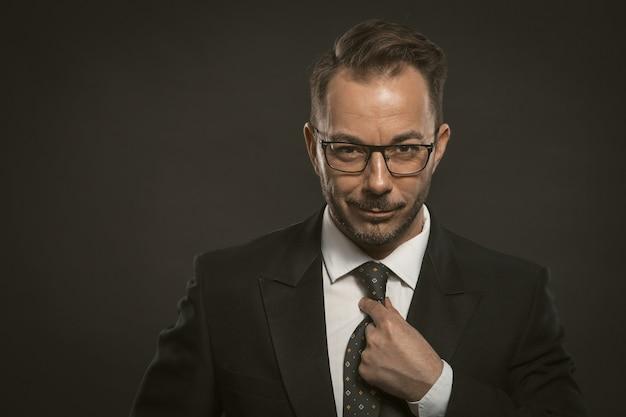 笑顔のビジネスマンは彼のネクタイをまっすぐにします。身なりの良いプロの銀行家が自信を持って見える