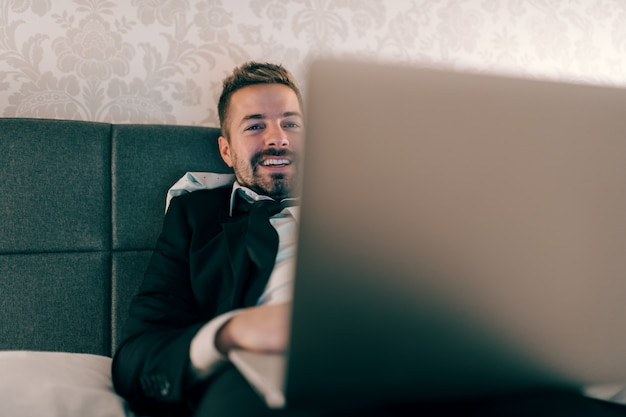 Smiling businessman in suit lying on the bed in hotel room at night and using laptop for work. overworking concept.