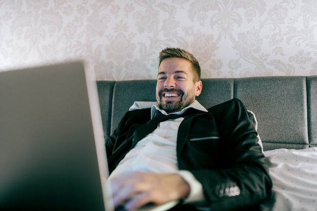 Smiling businessman in suit lying on the bed in hotel room at night and using laptop for work.