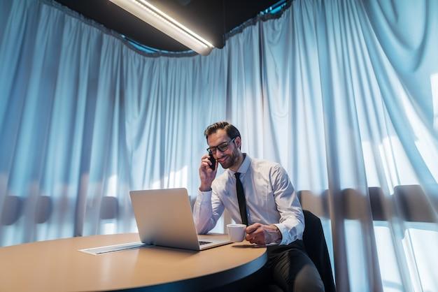 전화를 복용하고 회의실에 앉아있는 동안 커피를 마시는 웃는 사업가. 그 앞에서 책상 위에 노트북. 배경 커튼.