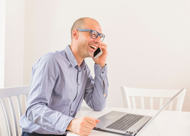 Smiling businessman talking on mobile phone with laptop on table