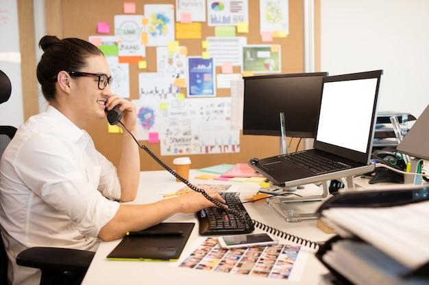 Улыбающийся бизнесмен разговаривает по телефону в творческом офисе